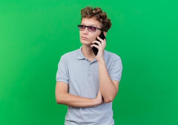 Молодой человек в черных очках в серой рубашке поло разговаривает по мобильному телефону и смотрит с серьезным лицом поверх зеленого