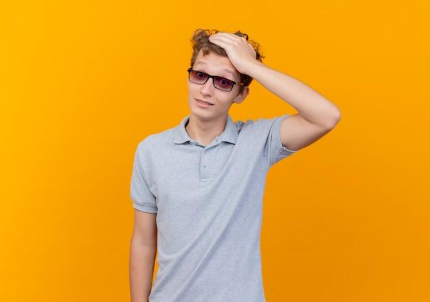 오렌지 벽 위에 서있는 실수로 그의 머리를 만지고 회색 폴로 셔츠를 입고 검은 안경에 젊은 남자