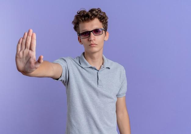 青い壁の上に立っている手で停止ジェスチャーをしている眉をひそめている顔と灰色のポロシャツを着ている黒い眼鏡の若い男
