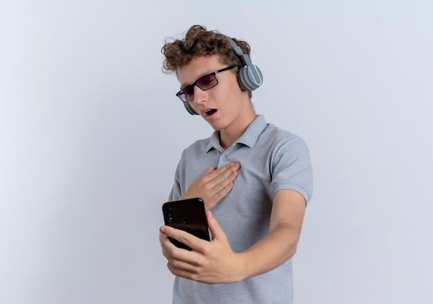 白い壁の上に立って感謝を感じて彼のスマートフォンの画面を見ているヘッドフォンで灰色のポロシャツを着ている黒い眼鏡の若い男