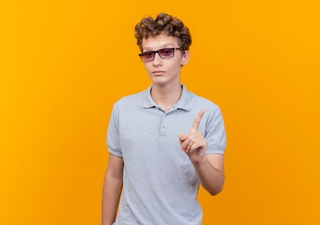 オレンジ色の壁の上に立っている人差し指の警告ジェスチャーを示す深刻な顔と灰色のポロシャツを着ている黒い眼鏡の若い男