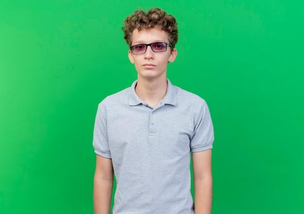 緑の壁の上に立っている深刻な顔と灰色のポロシャツを着ている黒い眼鏡の若い男