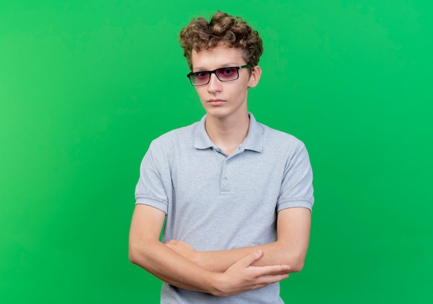 緑の壁の上に立っている交差した手で真面目な顔の灰色のポロシャツを着た黒い眼鏡の若い男
