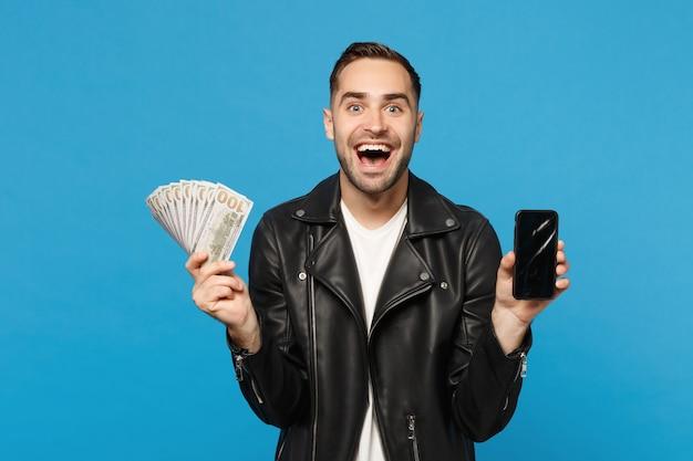 黒のジャケットの白いtシャツの若い男は、青い壁の背景のスタジオの肖像画に分離されたプロモーションコンテンツの現金のお金のために携帯電話の空の画面を保持します。人々のライフスタイルの概念。コピースペースのモックアップ