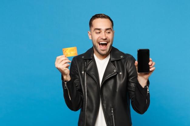 黒のジャケットの白いtシャツの若い男は、青い壁の背景のスタジオの肖像画に分離されたプロモーションコンテンツのクレジットカードの携帯電話の空の画面を保持します。ピープルライフスタイルコンセプトモックアップコピースペース