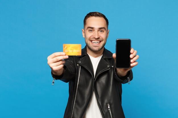Молодой человек в черной куртке и белой футболке держит пустой экран мобильного телефона для рекламного контента кредитной карты, изолированной на синем фоне стены. студийный портрет. концепция образа жизни людей макет копией пространства
