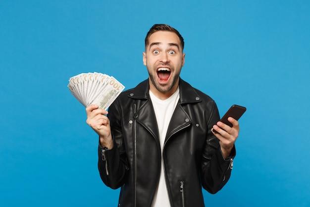 ドル紙幣の現金のファンを保持している黒い革のジャケット白いtシャツの若い男、青い壁の背景のスタジオの肖像画に分離された携帯電話。人々のライフスタイルの概念。コピースペースをモックアップします。