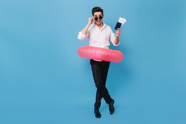 Молодой человек в черных штанах и белой рубашке счастливо позирует с резиновым кольцом. портрет парня в полный рост с паспортом и билетами на отдых.