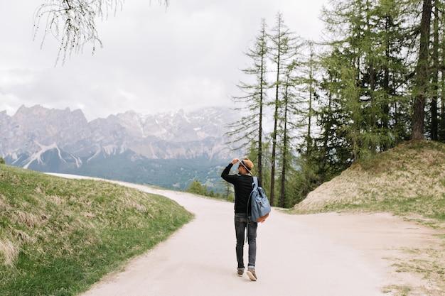 週末にイタリアの自然の景色を楽しみながら屋外で時間を過ごすバックパックを運ぶ黒いシャツを着た若い男