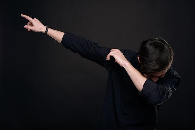 孤立した暗い背景に対して軽くたたく動きをしながら肘の曲がりくねった頭を落とす黒いシャツの若い男