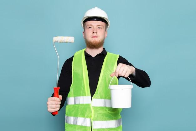 Молодой человек в черной рубашке зеленого и строительного костюма держит ведро с краской