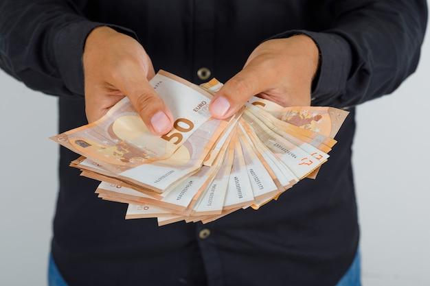 Молодой человек в черной рубашке держит банкноты евро