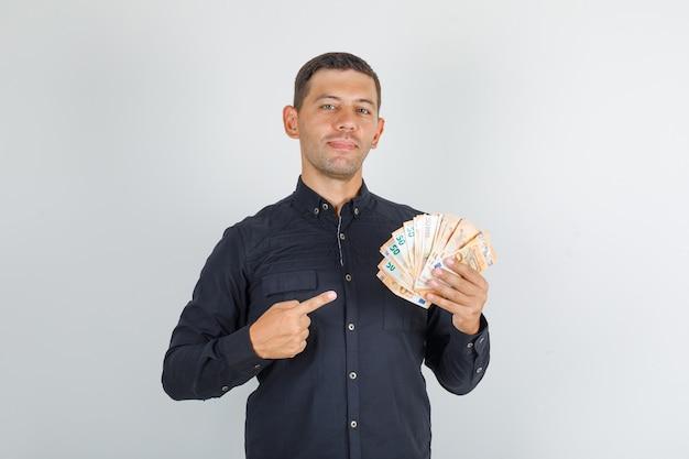 Молодой человек в черной рубашке, указывая пальцем на банкноты евро