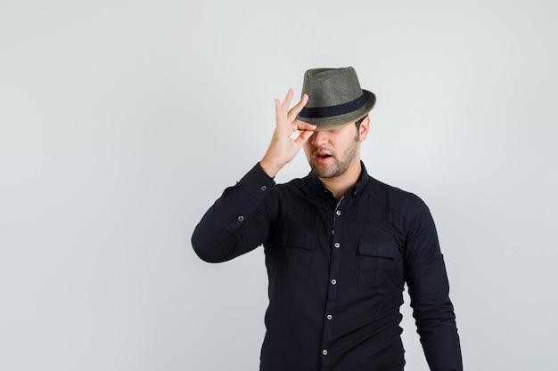 그의 모자를 아래로 당기고 세련된 찾고 검은 셔츠에 젊은 남자