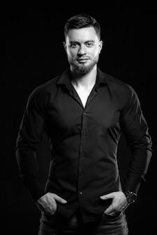 暗い背景に孤立した笑顔の黒いシャツを着た若い男。ポケットに立っている手。筋肉の男性、運動。ファッションポートレート