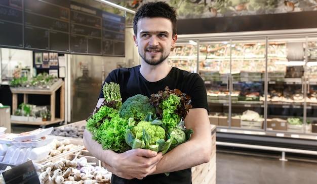 市場で緑の野菜だけを買う黒のtシャツの若い男