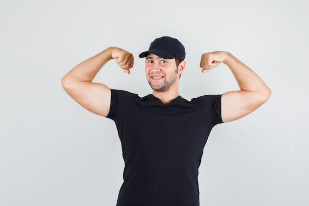 Молодой человек в черной футболке, кепке показывает мышцы и выглядит веселым