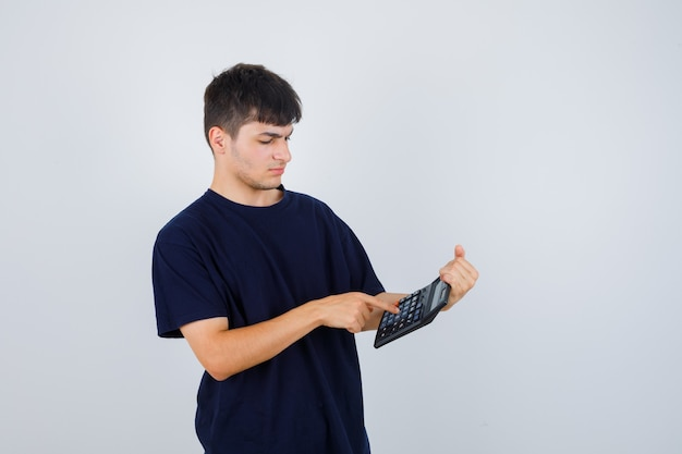 黒のtシャツを着た若い男が電卓で計算をし、忙しく見える、正面図。