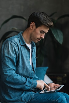 Young man in blue denim shirt using digital tablet