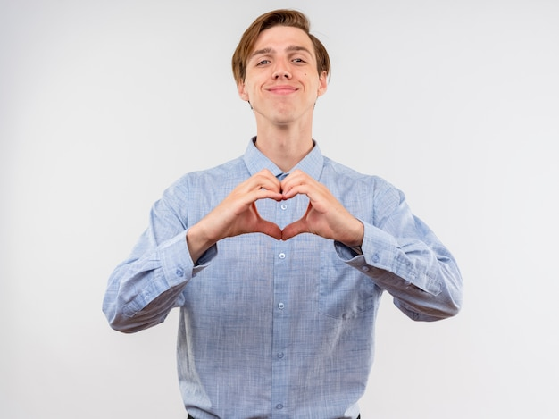 흰 벽 위에 서있는 행복한 얼굴로 웃는 손가락으로 파란색 심장 제스처를 만드는 젊은 남자