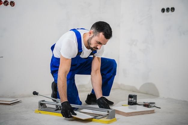 Молодой человек в синем комбинезоне режет плитку специальным инструментом