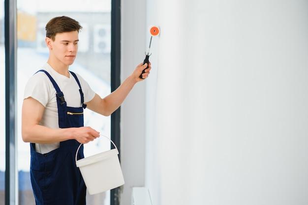 ローラーで壁を白い色に塗る青いオーバーオールの若い男