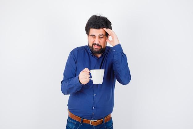 파란색 셔츠와 청바지 컵을 들고 이마에 손을 넣고 지쳐, 전면보기에 젊은 남자.