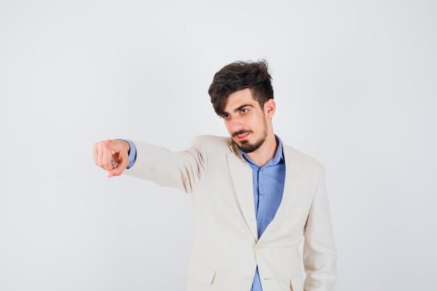 青いシャツと白いスーツのジャケットの若い男は拳を握りしめ、幸せそうに見えます