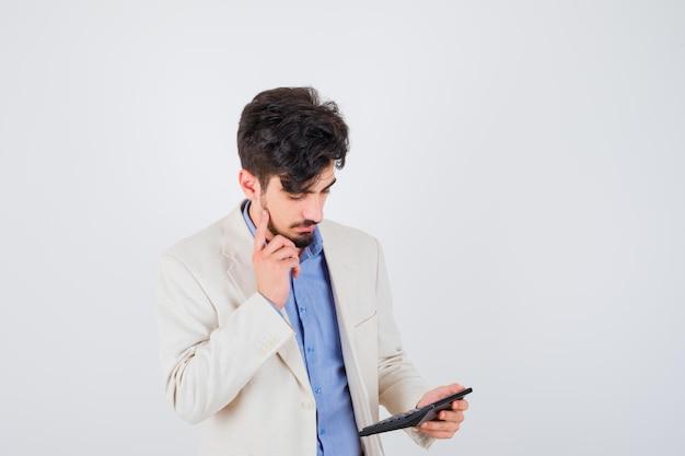 青いシャツと白いスーツのジャケットを着た若い男が電卓を見て、考えているポーズで立って、集中して見える