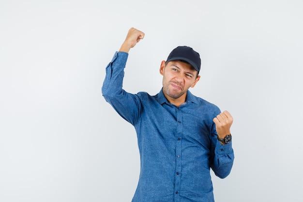 Молодой человек в голубой рубашке, кепке показывает жест победителя и выглядит счастливым, вид спереди.