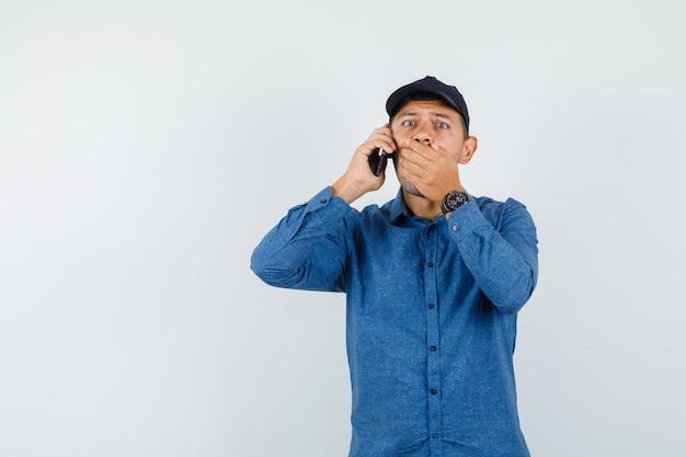 青いシャツを着た若い男、携帯電話で話しているキャップ、驚いて見える、正面図。