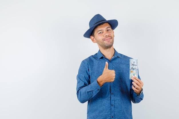 青いシャツを着た若い男、親指を立ててドル紙幣を持って陽気に見える帽子、正面図。