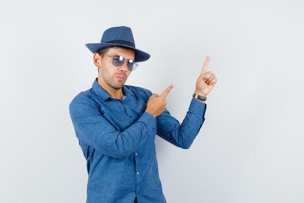 파란색 셔츠를 입은 청년, 모자를 위로 가리키고 자신감을 보이는 전면 전망.