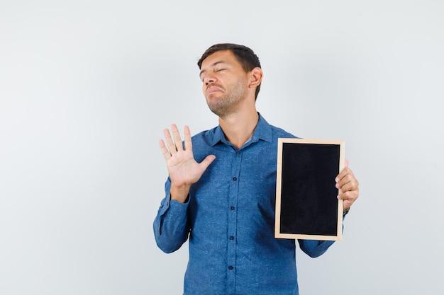 파란색 셔츠를 입은 젊은 남자가 몸짓 없이 칠판을 들고 기운이 없고 앞모습을 보고 있습니다.
