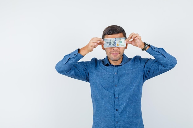 Молодой человек в голубой рубашке держит долларовую купюру на глазах и выглядит смешно, вид спереди.
