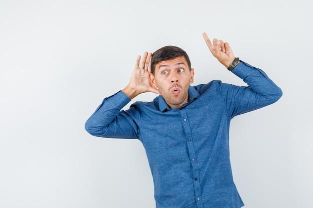 파란색 셔츠를 입은 젊은 남자가 귀 뒤에 손을 잡고 가리키며 놀란 표정을 짓고 있습니다.