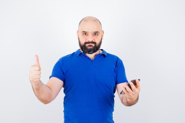 파란색 셔츠를 입은 젊은 남자가 전화를 들고 엄지손가락을 치켜들고 정면을 바라보고 있습니다.