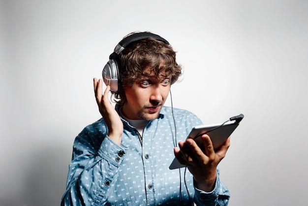 タブレットを保持し、ヘッドフォンを身に着けている青いシャツの若い男