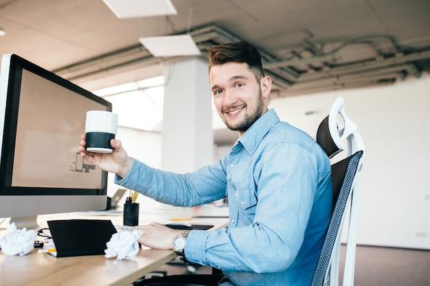 Молодой человек в голубой рубашке сидит на своем рабочем месте в офисе. он носит синюю рубашку. он держит чашку и улыбается в камеру.