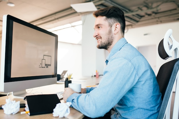 Молодой человек в голубой рубашке сидит на своем рабочем месте в офисе. он носит синюю рубашку. он держит чашку и улыбается в сторону.