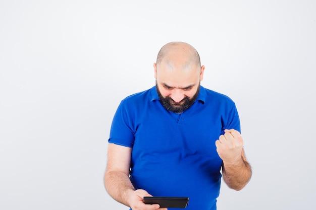 파란 셔츠를 입은 청년이 계산기를 쳐다보며 주먹을 들고 즐거운 표정을 짓고 있습니다.