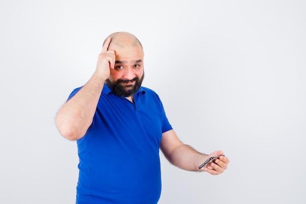 彼の頭を指して、希望に満ちた正面図を見ながら電話を見ている青いシャツを着た若い男。