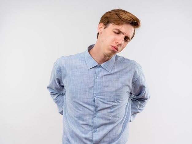 青いシャツを着た若い男は、白い背景の上に立っている痛みを感じて背中に触れて目を閉じて不満を感じている