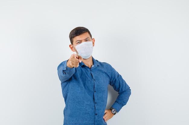 파란색 셔츠를 입은 젊은 남자, 카메라를 가리키고 진지한 정면을 바라보는 마스크.