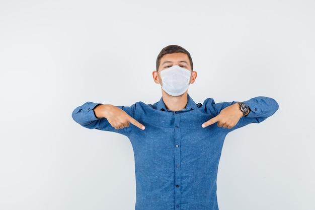 파란색 셔츠를 입은 청년, 마스크가 자신을 가리키고 자랑스러워 보이는 앞모습.