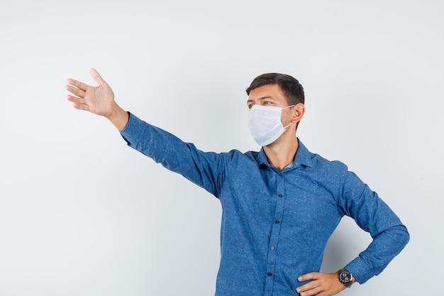 파란색 셔츠를 입은 청년, 앞을 바라보면서 누군가에게 외치는 마스크.