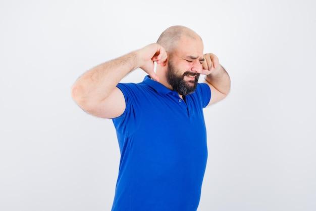 青いシャツを着た若い男が指で耳を塞ぎ、緊張しているように見えます。