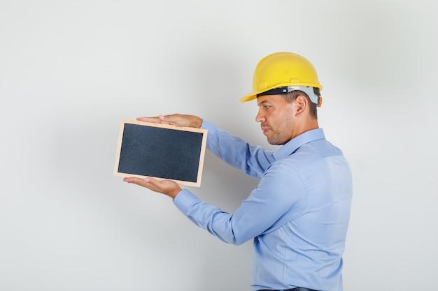 青いシャツ、安全ヘルメットの黒板を押しながら希望に満ちた探している若い男