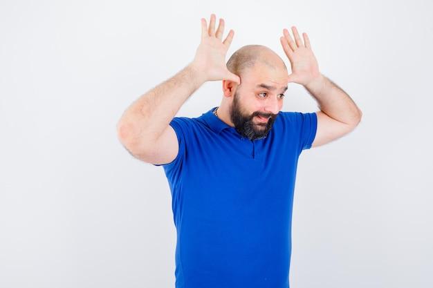青いシャツを着た若い男が頭上に角のサインを見せて、面白そうに見えます。
