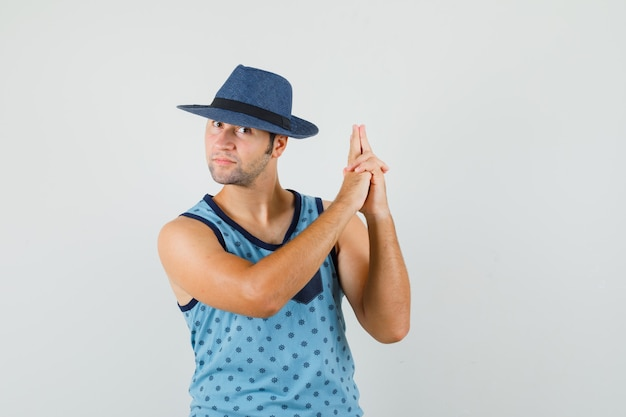 파란색 중항, 모자 촬영 제스처를 만들고 자신감을 찾는 젊은 남자